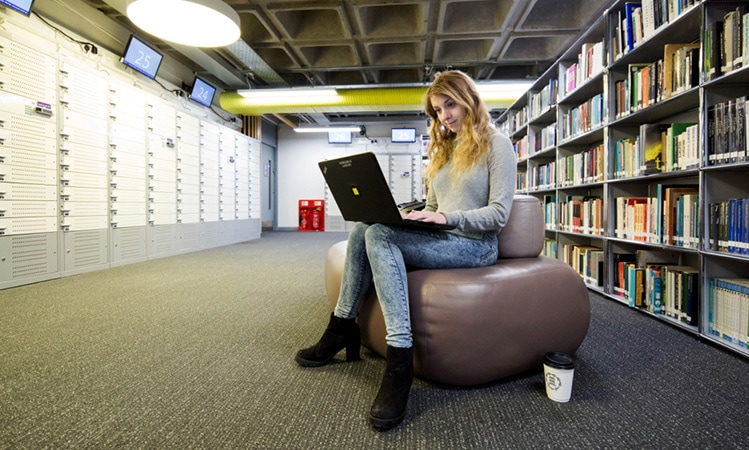 a student with lenovo pc in library