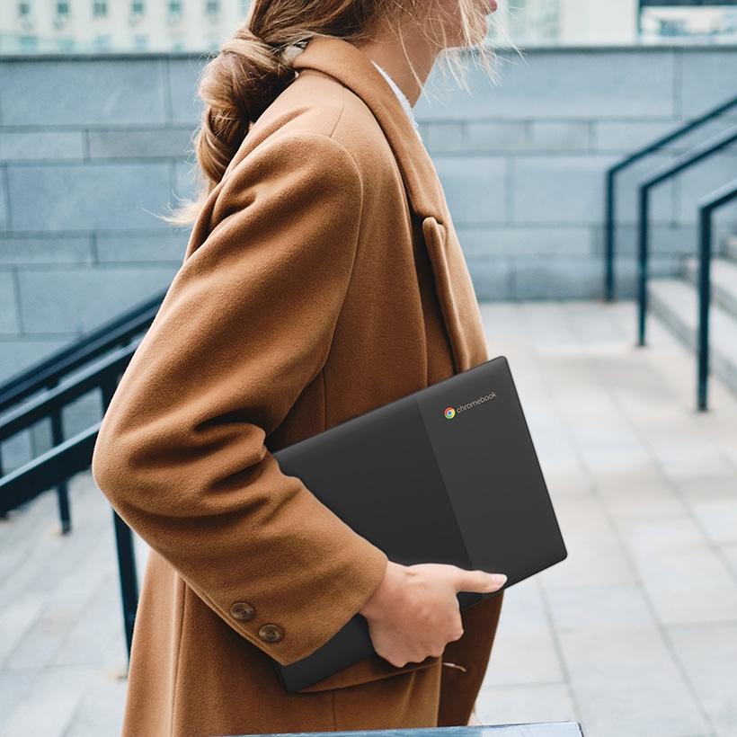 Mujer llevando su Lenovo Chromebook bajo el brazo