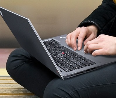 A Lenovo laptop on a person's lap