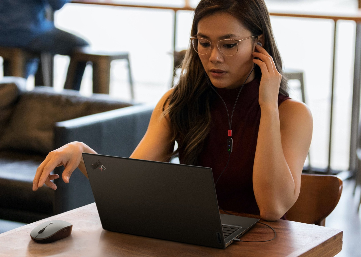 Woman using Lenovo Go accessories set up on a table at a coffee shop