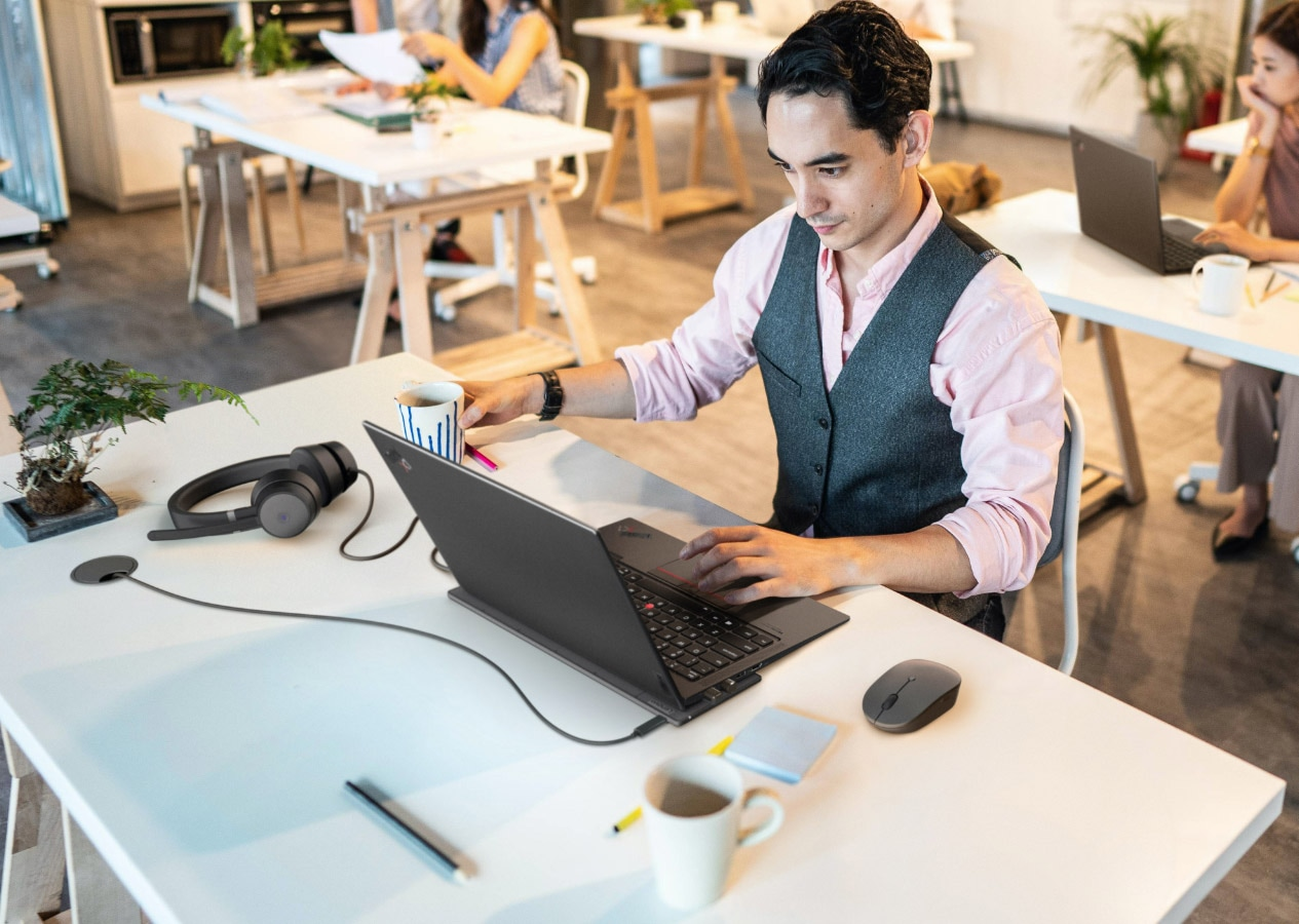 Man using Lenovo Go accessories in a shared office environment