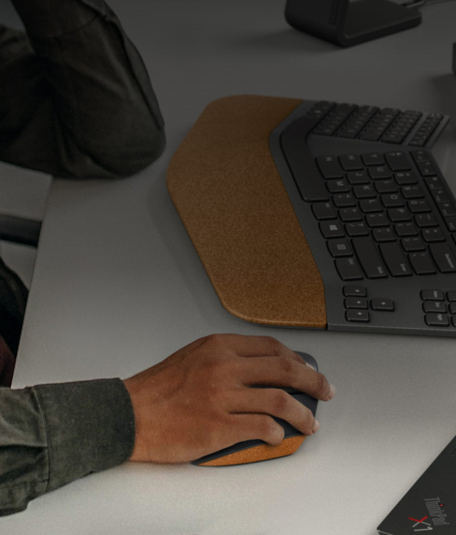 Lenovo Go Wireless Vertical Mouse in a user's hand on a desk.