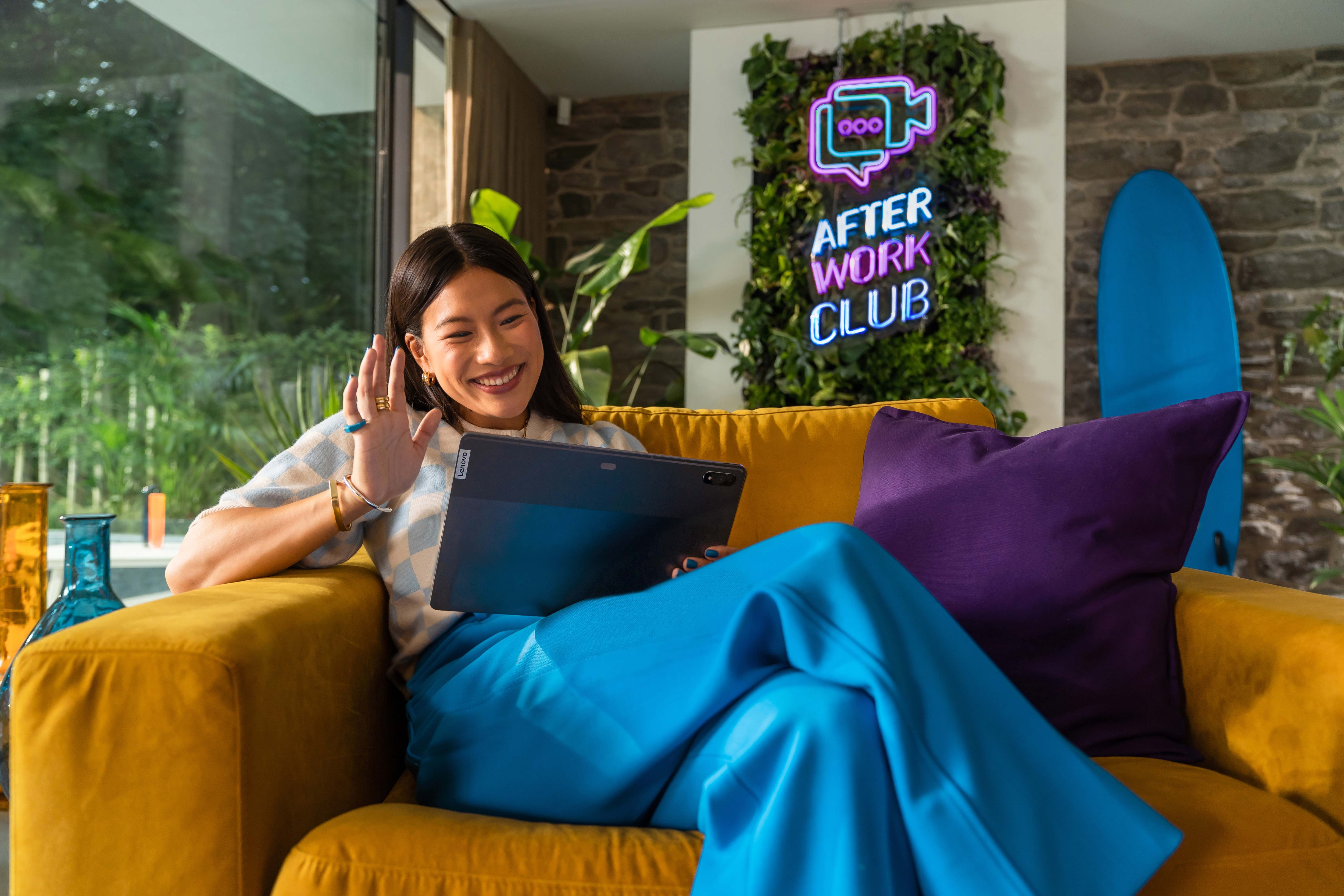 Woman relaxing in her After Work Club on a sofa set, wave hello to online friends on her Lenovo tablet