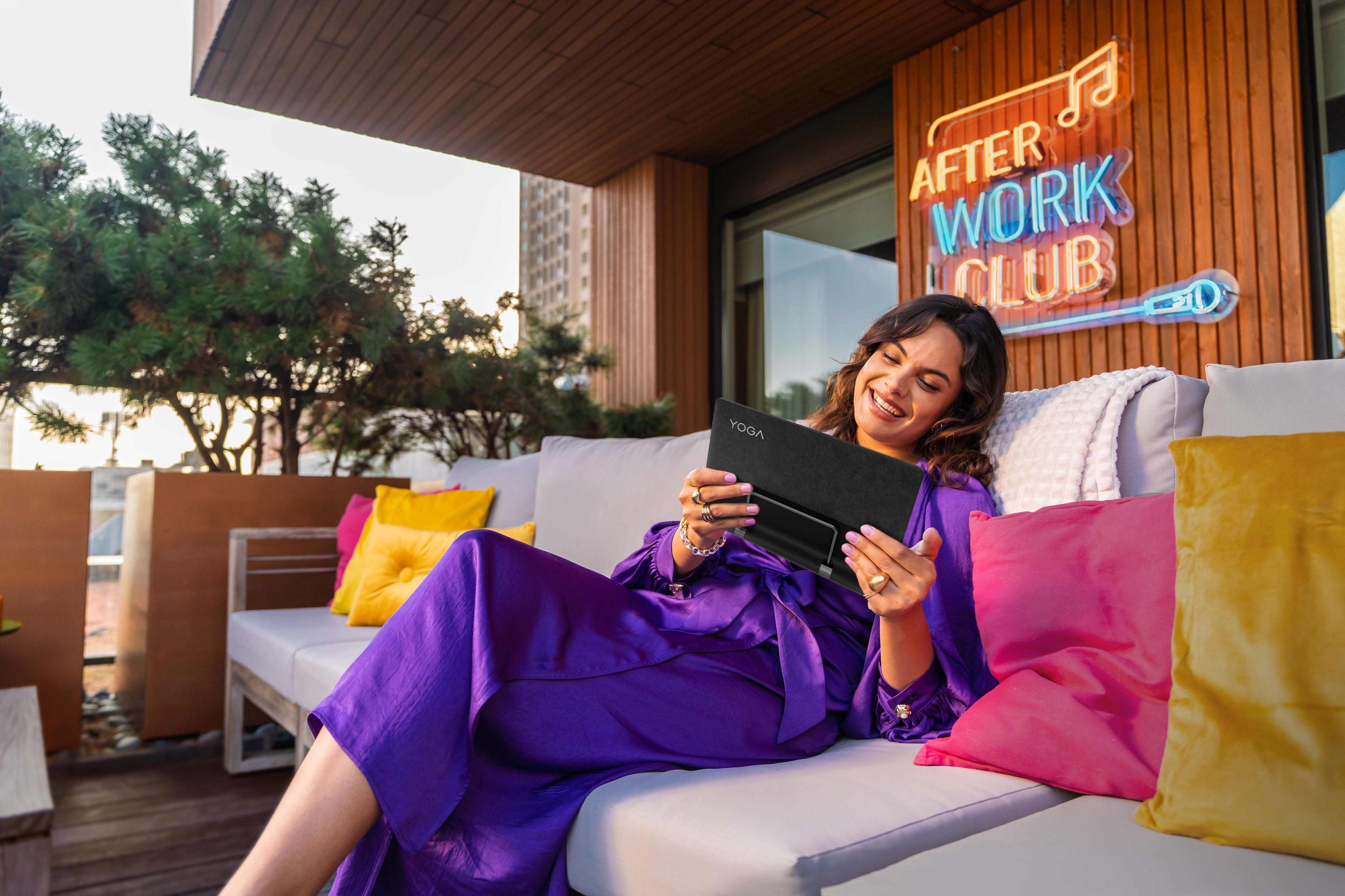 Woman relaxing on her outdoor couch, enjoying viewing content on her Lenovo Tablet.