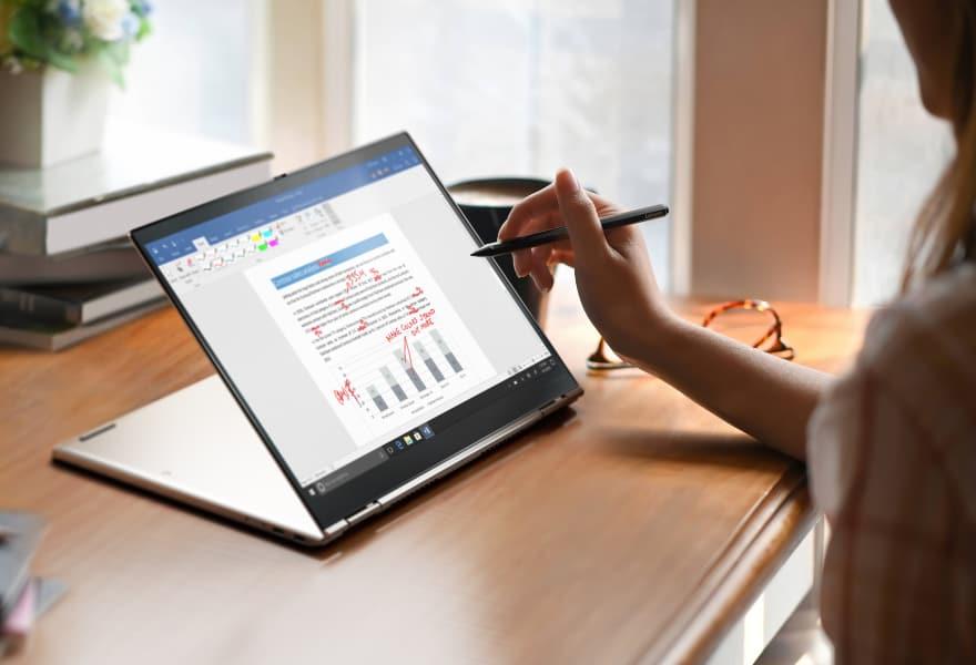 Document d'édition femme sur Lenovo ThinkPad X1 Titanium Yoga en utilisant un stylo tactile pour dessiner sur l'écran
