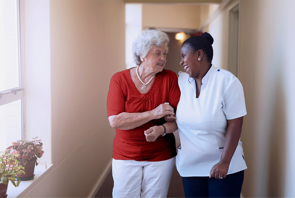 a nurse and an old woman smiling and talking