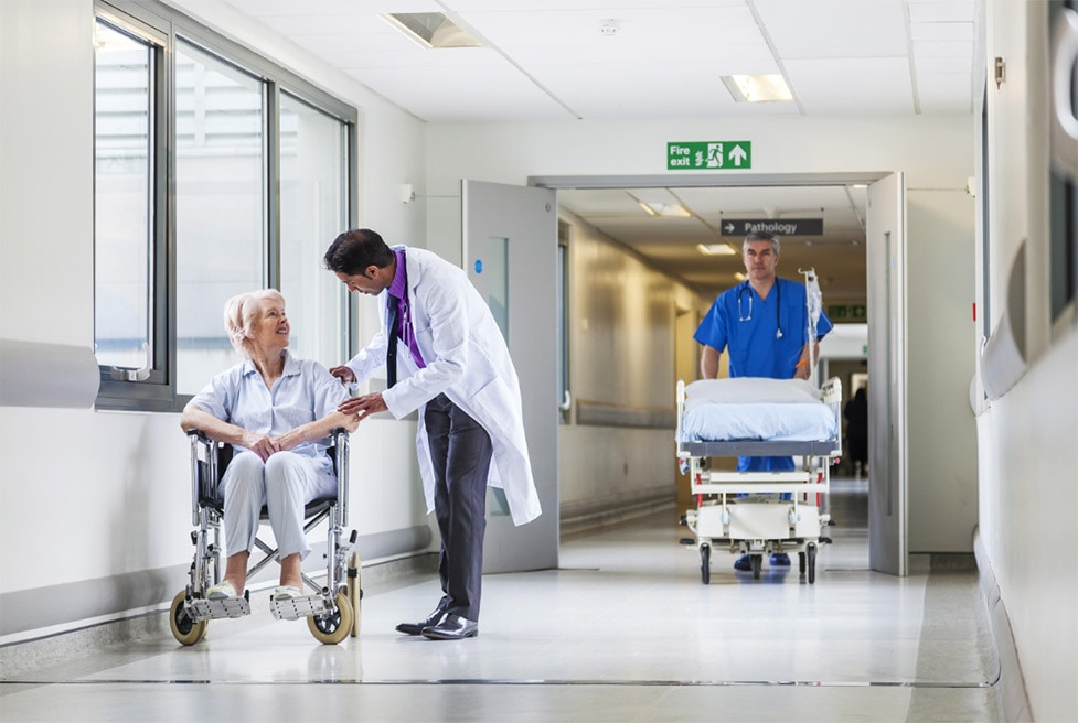 a hospital corridor with a doctor talking to a patient in a wheelchair